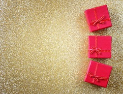 red gift boxes on glitter gold background