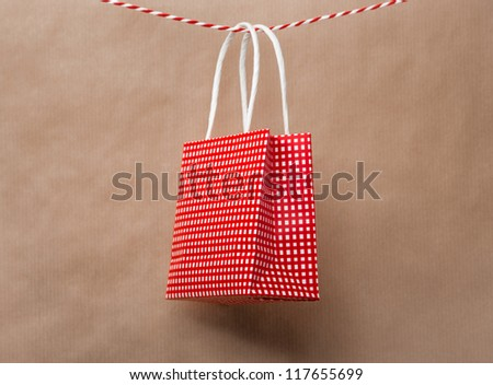 Red gift package paper bag hanging on a ribbon. Old brown paper background