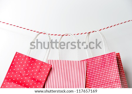 Red gift package paper bags hanging on a ribbon