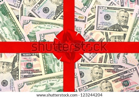 red gift ribbon with bow over american dollars. money background. shopping gift card concept