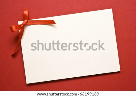 red gift tag tied with a bow of red satin ribbon