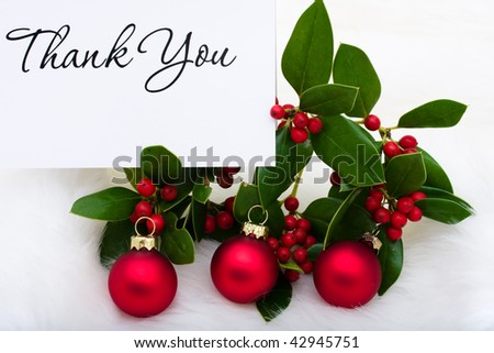 Red glass balls with a thank you card and holly and berries on a white fur background, Christmas balls