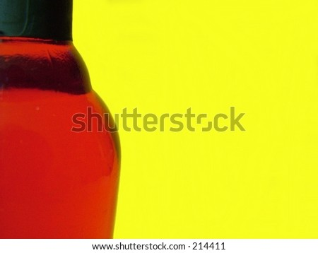 Red Glass Bottle against Yellow Background