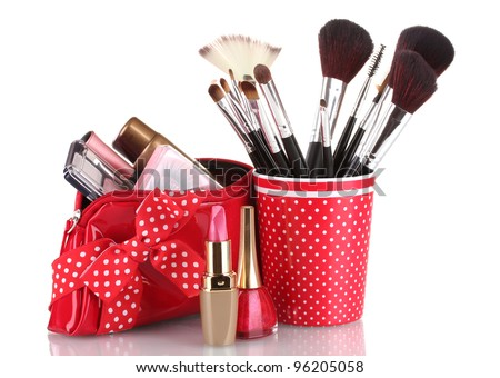 red glass with brushes and makeup bag with cosmetics isolated on white