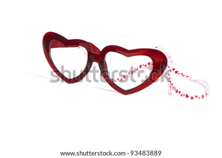 red glasses with heart shape glass and ribbon isolated on white