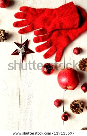 Red gloves with Christmas ornaments on white wood background