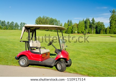 Red golf cart over nice green and blue sky