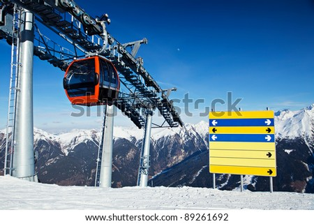 Red gondola ski lift and blank direction's billboard in mountains ski resort