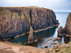 Red granite cliffs and sea stack on Muckle Roe, Shetland, UK - these rocks are of the Muckle Roe Intrusion - granite, granophyric - igneous Devonian bedrock formed 359 to 383 million years ago.