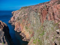 Red granite cliffs on Muckle Roe, Shetland, UK - these rocks are of the Muckle Roe Intrusion - granite, granophyric - igneous bedrock formed 359 to 383 million years ago in the Devonian Period.