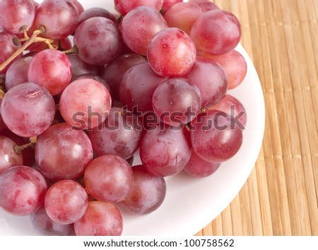 Red grape berries in white plate on straw tray closeup