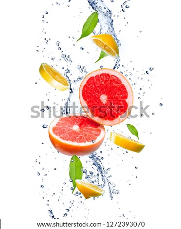 Red grapefruits and yellow lemons in a splash of water. Grapefruit and lemon in motion. Tropical fruit concept.