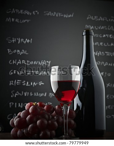Red grapes, a bottle, a glass of wine and blackboard. Low-angle shot Stockfoto ©