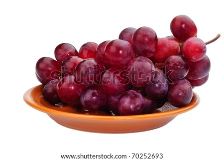 Red grapes on a brown dish. Isolated on white.