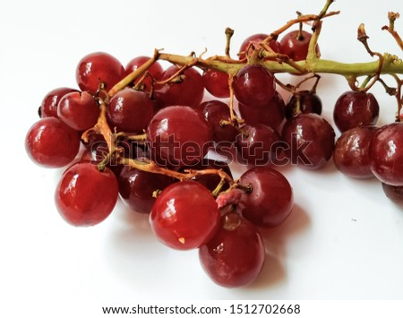 Red grapes resting on a white ground, gooseberry with a sweet and sour taste.
