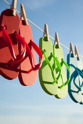 Red, green and blue flip-flops hanging on a line with a sky background