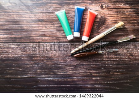 Red, green and blue paint tubes with paintbrushes in the wooden background #1469322044
