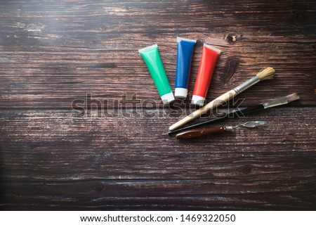 Red, green and blue paint tubes with paintbrushes in the wooden background #1469322050