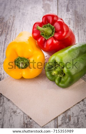 Red, green and yellow colored bell peppers on the wooden table
