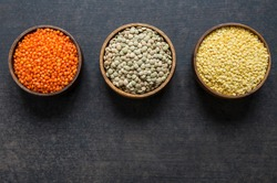 Red, green and yellow lentils in wooden bowl on grey rustic background, uncooked various dried lentil legumes
