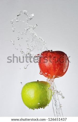Red, green apples and water splash