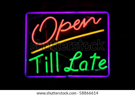 Red, green, purple and yellow neon sign of the words 'open till late' on a black background.