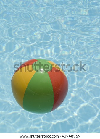 red green yellow beach ball floating in a swimming pool.