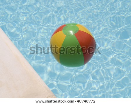 red green yellow beach ball floating in a swimming pool near the edge.