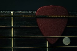 red guitar pick tucked into gold acoustic guitar strings on a dark wood fret board.