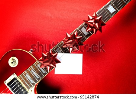Red guitar with red ribbon bows and white blank card on neck fret board. Concept image for invitation to a holiday musical event or, a  christmas present electric guitar.