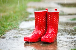 Red gumboots in rain full of water