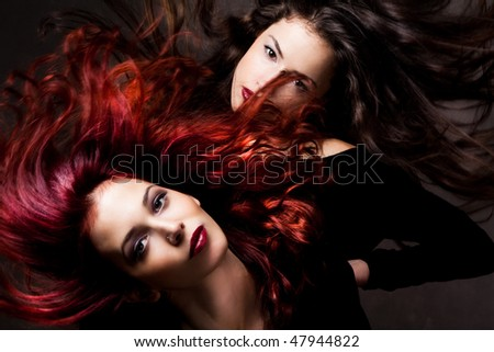 red hair and brunette woman with hair in motion, studio shot
