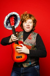Red-hair funny teenage boy playing little guitar, isolated on vivid red background