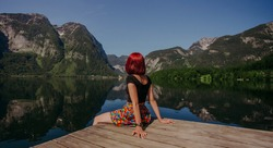 Red hair Girl with color skirt enjoying amazing view of mountains reflected in lake of Fairy tale village Hallstatt.