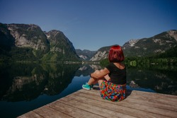 Red hair Travel Girl with color skirt enjoying amazing view of mountains reflected in lake of Fairy tale village Hallstatt.