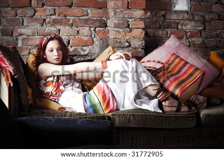 red hair woman in summer clothes resting on sofa