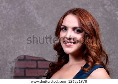 Red hair woman with blue dress in front of dark background.