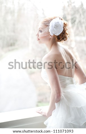 Red haired bride leans against porch railing, looking contemplative.