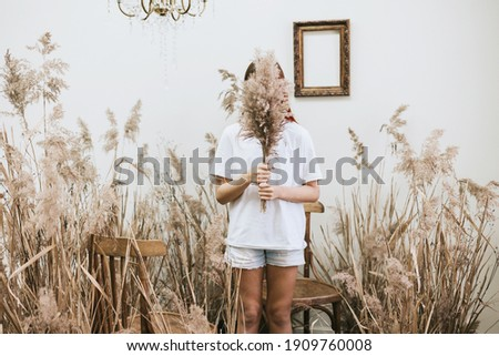 red haired girl closes her face with bouquet wearing a white shirt and denim shorts in a space decorated with dry grass and flowers in a retro style