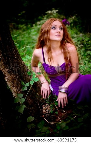 red-haired girl collecting mushrooms in wood