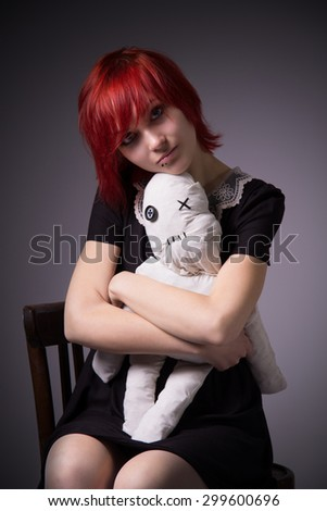 Red-haired girl, dress with lace collar, rag doll sitting on a chair, hugging a doll, blue eyes, vintage image, vertical photo, gradient background.