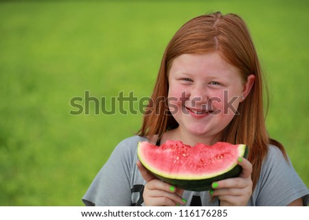 Red-haired girl eating a watermelon on a green meadow. Blurred background.