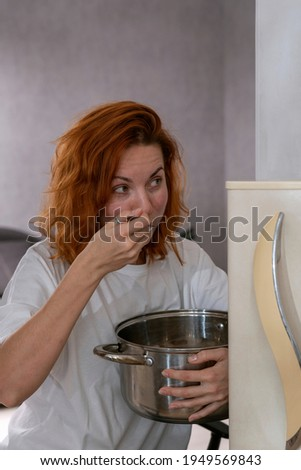 Red-haired girl eats from large saucepan near the refrigerator Stock photo ©