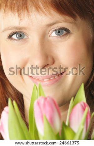 Red-haired girl face closeup with pink tulips on foreground