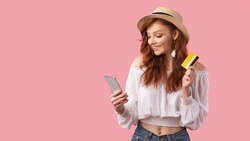 Red-Haired Girl Holding Phone And Credit Card Using Mobile Shopping App Standing On Pink Studio Background. Panorama, Copy Space