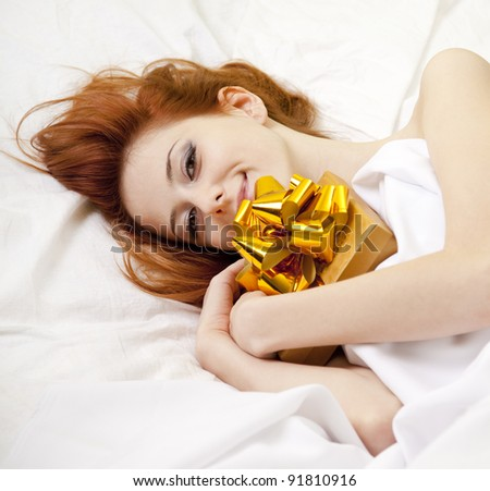 Red-haired girl in bed with gift. Studio shot.