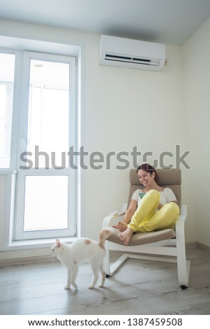 Red-haired girl in bright clothes and barefoot sits in a chair with a phone in her hands under the air conditioner. Young woman sitting in an armchair with a cat #1387459508