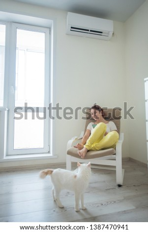 Red-haired girl in bright clothes and barefoot sits in a chair with a phone in her hands under the air conditioner. Young woman sitting in an armchair with a cat #1387470941
