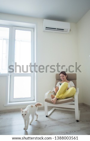 Red-haired girl in bright clothes and barefoot sits in a chair with a phone in her hands under the air conditioner. Young woman sitting in an armchair with a cat #1388003561