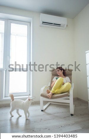 Red-haired girl in bright clothes and barefoot sits in a chair with a phone in her hands under the air conditioner. Young woman sitting in an armchair with a cat